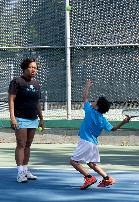 Veronica Badon teaching young student on court